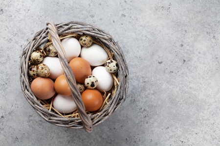 Hen and quail eggs in basket on stone table. Easter greeting card. Top view with space for your greetings Standard-Bild - 116246711