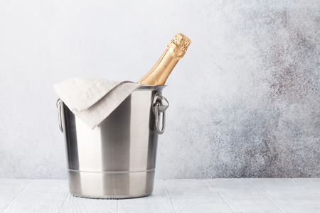 Champagne bottle in bucket in front of stone wall. With space for your text
