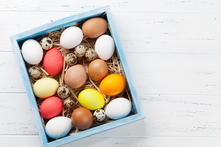 Easter greeting card with colorful eggs in box on white wooden table. Top view with space for your greetings Stockfoto