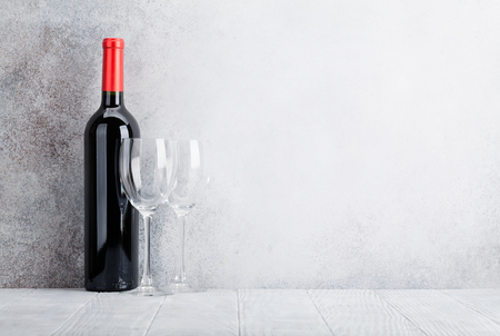 Red wine bottle and glasses in front of stone wall. With space for your text