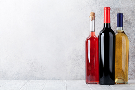 Red, rose and white wine bottles in front of stone wall. With space for your text