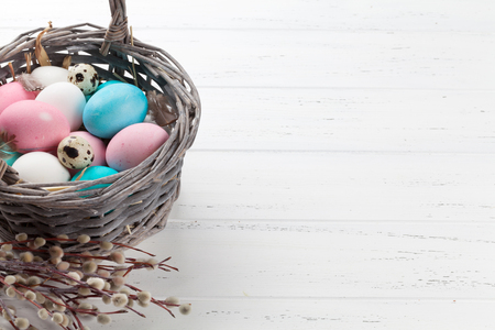 Easter greeting card with colorful eggs in basket on white wooden table. With space for your greetings