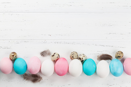 Easter greeting card backdrop with colorful eggs on white wooden table. Top view with space for your greetings Stock Photo