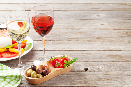 White and rose wine glasses with caprese salad. Traditional italian antipasti. With space for your text