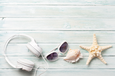 Travel vacation and music concept with headphones, seashell and sunglasses on wooden backdrop. Top view with copy space. Flat lay