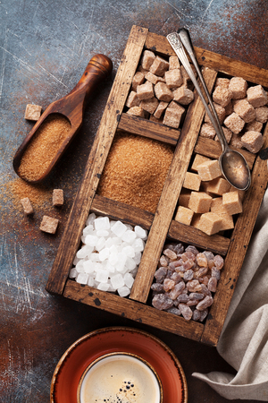 Various brown and white sugar in wooden box and coffee cup. Top view