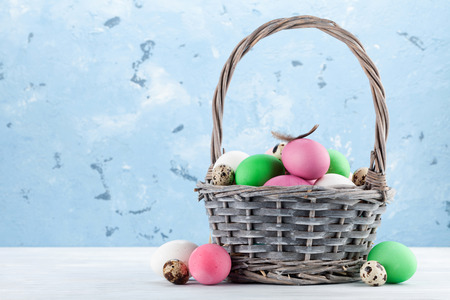 Easter greeting card with colorful easter eggs in basket. In front of stone wall with space for your greetings