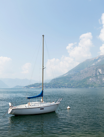 Sailing boat on Como lake in front of mountains