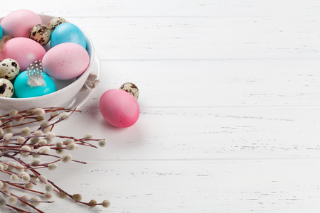 Easter greeting card with colorful eggs in bowl on white wooden table. With space for your greetings