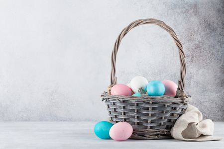 Easter greeting card with colorful easter eggs in basket in front of stone wall. With space for your greetings Stock Photo