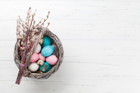 Easter greeting card with colorful eggs in basket on white wooden table. Top view with space for your greetings