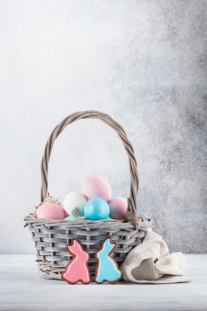 Easter greeting card with gingerbread cookies and colorful easter eggs in basket in front of stone wall. With space for your greetings
