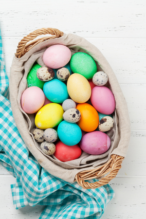 Easter greeting card with colorful eggs in basket. Top view on wooden table with space for your greetings