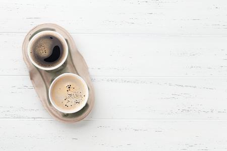 Dos tazas de café para llevar en la mesa de madera. Vista superior con espacio de copia para su texto. Foto de archivo
