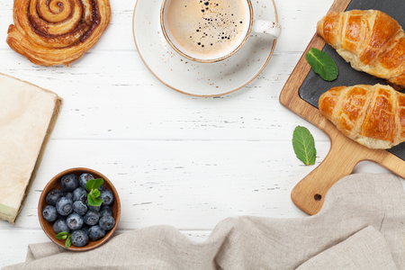 Coffee, croissants and berries breakfast. On wooden table. Top view with copy space for your text