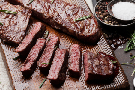 Top blade or denver grilled steak over cutting board