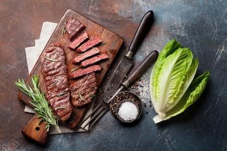 Top blade or denver grilled steak over cutting board and lettuce salad. Top view