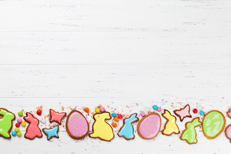 Easter greeting card with colorful gingerbread cookies, chocolate eggs and candies. Top view on wooden table with space for your greetings