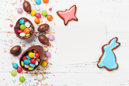 Easter greeting card with colorful gingerbread cookies, chocolate eggs and candies. Top view on wooden table with space for your greetings Standard-Bild - 117271920
