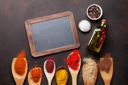 Set of various spices and herbs on stone background. Top view with chalkboard for your recipe. Flat lay