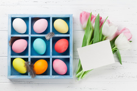 Easter greeting card with tulip flowers and colorful easter eggs. Top view on wooden table with space for your greetings