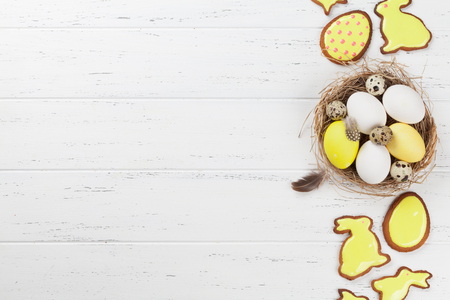 Easter eggs and gingerbread cookies on wooden table. Rabbits, butterflies and eggs. Greeting card backdrop. Top view with space for your greetings Stock Photo