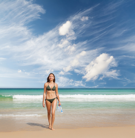 Young attractive woman relax on the sea beach. Bright sand, blue sky and crystal sea. Tropical beach vacation concept. With copy space