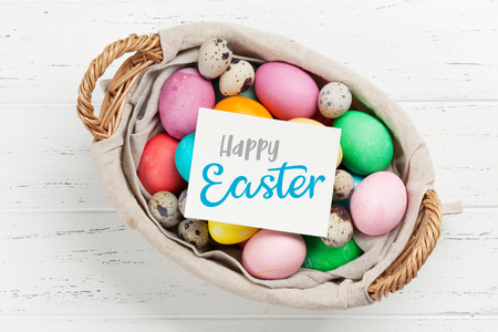 Easter greeting card with colorful easter eggs in basket. Top view on wooden table with space for your greetings Stock Photo