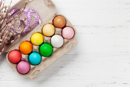 Easter greeting card with colorful easter eggs on wooden table. Top view with space for your greetings