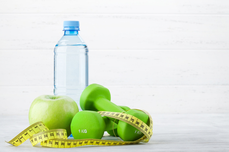 Fitness and healthy food concept. Dumbbells, apple and drink bottle. With copy space for your text Stock Photo