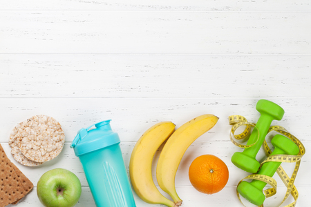 Fitness and healthy food concept. Dumbbells, fruits and drink bottle on wooden table. Top view with copy space for your text