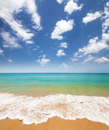 Summer sand beach, tropical sea waves and blue sky with clouds. Perfect vacation place landscape