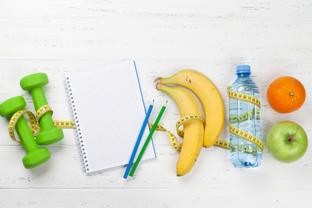 Fitness and healthy food concept. Dumbbells, fruits and notepad on wooden table. Top view with copy space for your text