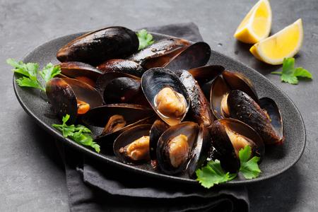 Délicieuses moules de fruits de mer cuites avec sauce tomate, persil et citron Banque d'images
