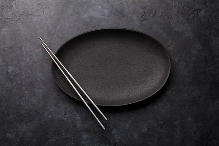 Plato vacío y palillos sobre mesa con textura negra. Plantilla de comida japonesa. Vista superior con espacio de copia. Endecha plana Foto de archivo