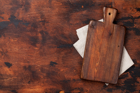 Cooking wooden table with cutting board over kitchen towel or napkin. Top view with space for your meal or recipe