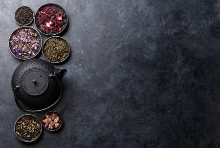 Various dry tea assortment and teapot. Black, green and herbal tea. Top view with space for your text