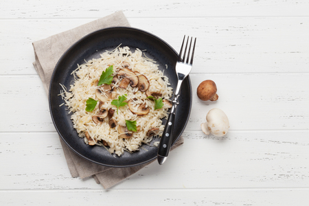 Delicious mushrooms risotto dressed with parmesan cheese and parsley. Top view with copy space for your text
