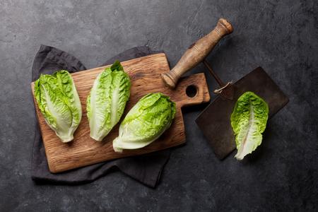 Mini romaine lettuce salad on stone kitchen table. Top view