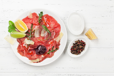 Marbled beef carpaccio with arugula, lemon and parmesan cheese. Top view, flat lay Zdjęcie Seryjne