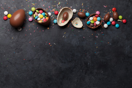 Easter greeting card with chocolate eggs and colorful candies. Top view on stone table with space for your greetings Stock Photo
