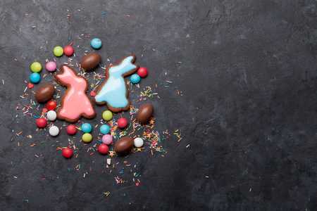 Easter greeting card with colorful gingerbread cookies, chocolate eggs and candies. Top view on stone table with space for your greetings