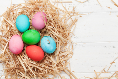Easter greeting card with colorful eggs. Top view on wooden table with space for your greetings