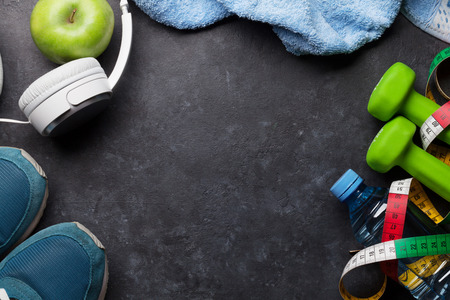 Fitness concept. Dumbbells, sneakers, headphones and apple on stone Stock Photo
