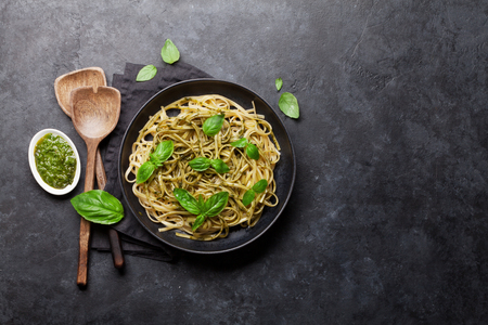 Spaghetti pasta with pesto sauce, parmesan cheese and fresh basil. Top view with copy space for your text 스톡 콘텐츠