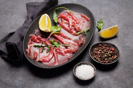 Marbled beef carpaccio with arugula, lemon and pepper. Closeup