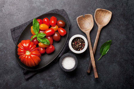 Fresh garden tomatoes, spices and basil on plate over stone cooking table. Top view
