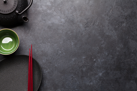 Empty plate, cup, teapot and chopsticks over black textured table.