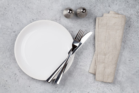 Table setting. Empty plate, knife, fork, spices and napkin. Top view and flat lay with copy space Banque d'images - 119497588