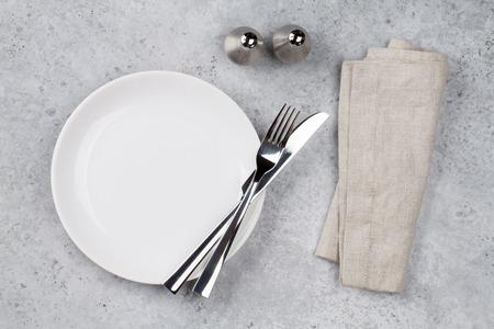 Tafel opstelling. Lege plaat, mes, vork, kruiden en servet. Bovenaanzicht en plat leggen met kopieerruimte